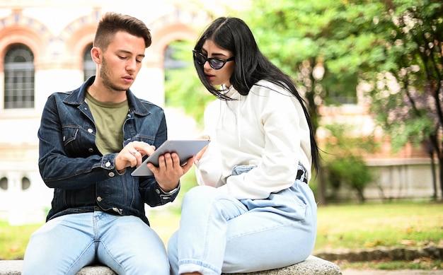 Twee studenten studeren samen met een digitale tablet zittend op een bankje buiten