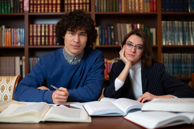 Twee studenten zitten naast een set boeken. foto van het onderwijsproces