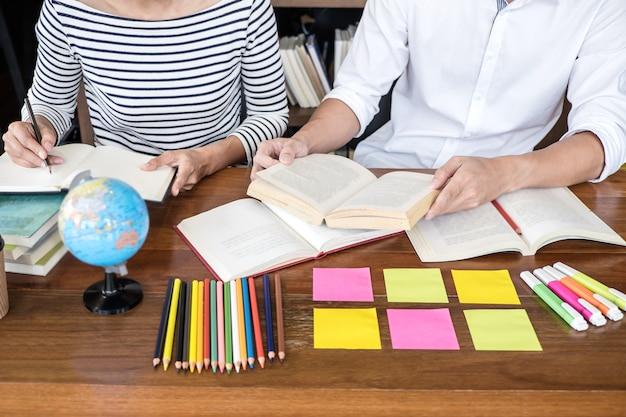 Twee studentengroep van de middelbare schoolzitting in bibliotheek met hulpvriend die thuiswerk en lessenpraktijk doet