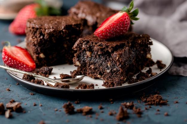 Twee stukjes chocolade brownie, close-up, op schotel met plakjes aardbeien, kruimels. donkerblauwe achtergrond