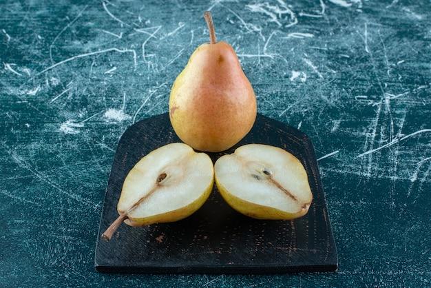 Twee stukjes peren op het bord, op de blauwe achtergrond. hoge kwaliteit foto