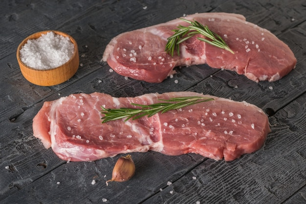 Twee stukjes varkensvlees met rozemarijn en een bakje grof zeezout. ingrediënten voor het koken van vleesgerechten.