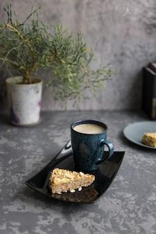 Twee stukken amandelcake en mok koffie op zwart presenteerblad