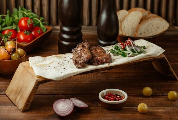 Twee stukken biefstuk geserveerd in lavash met soorten