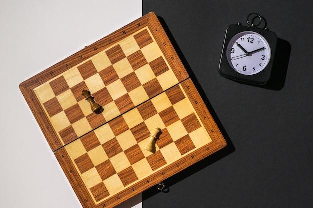 Twee stukken, een schaakbord en een klok op een zwart-witte achtergrond.
