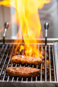 Twee stukken gemarineerd rundvlees geroosterd op kolen op de grill