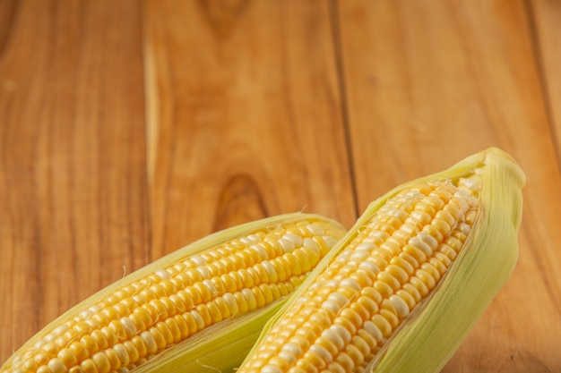 Twee stukken maïs geplaatst op een houten tafel.