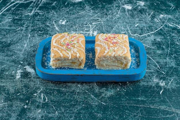 Twee stukken roll cake op houten plaat, op de blauwe tafel.