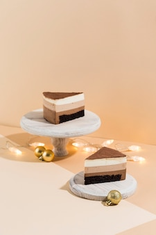 Twee stukken van chocoladebiscuitgebak op witte houten tribunes met kerstmisslingers