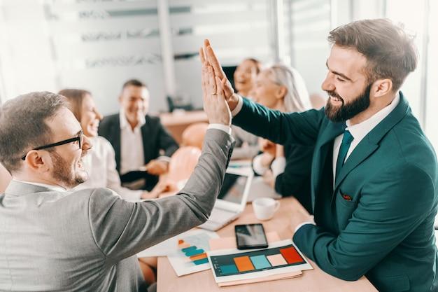 Twee succesvolle, glimlachende architecten in formele kleding geven high five terwijl ze in de directiekamer zitten. op de achtergrond chatten collega's. gemiddeld wordt niet gevierd.