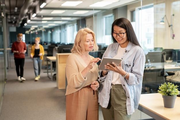 Twee succesvolle interculturele zakenvrouwen bespreken ideeën voor een nieuw werkproject terwijl ze door online bedrijfsrecensies scrollen