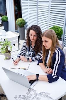 Twee succesvolle jonge zakelijke vrouwelijke managers zitten aan een tafel met een laptop en een notebook en werken aan een nieuw ontwikkelingsproject, vrouwelijke studenten schrijven een rapport over het werk van hun computer