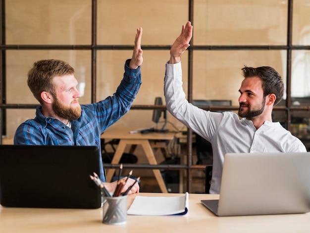 Twee succesvolle mannelijke collega die hoge vijf in bureau geeft
