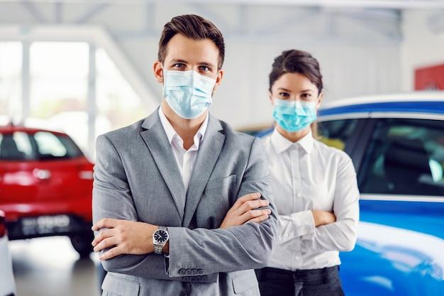 Twee succesvolle, trotse autoverkopers staan met gekruiste armen in de autosalon en hebben gezichtsmaskers op gezichten
