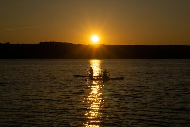 Twee surfers zitten en roeien op stand-up paddleboards tegen de achtergrond van de ondergaande zon