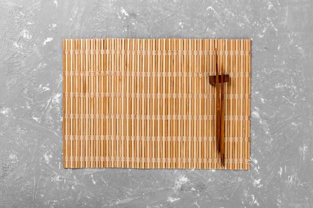 Twee sushi eetstokjes met lege bruine bamboe mat of houten plaat op cement achtergrond bovenaanzicht met copyspace. lege aziatische voedselachtergrond