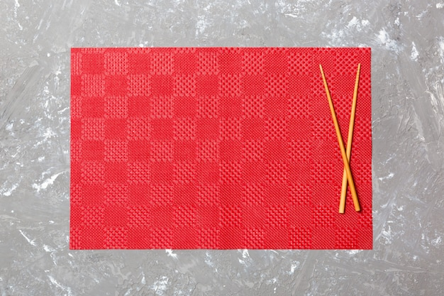 Twee sushi eetstokjes met lege rode tafellaken, servet op cement bovenaanzicht met copyspace. lege aziatische voedselachtergrond