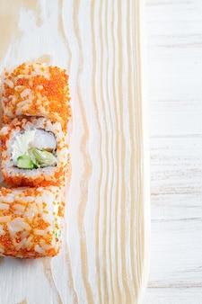 Twee sushibroodjes met garnalen op houten plaat.