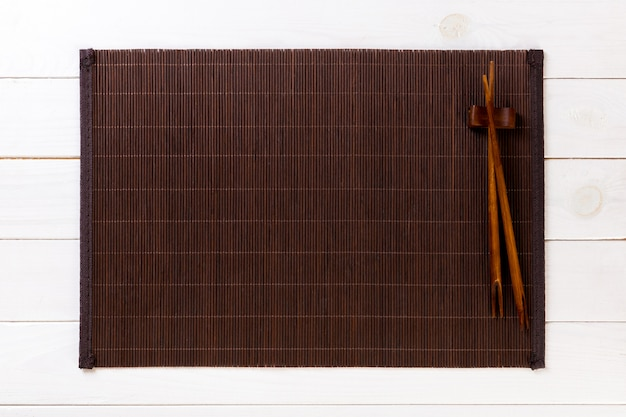 Twee sushieetstokjes met lege bamboemat of houten plaat op witte houten hoogste mening als achtergrond met exemplaarruimte. leeg aziatisch eten