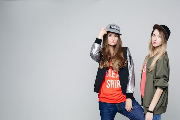 Twee swag hipster meisjes vertrouwen poseren.