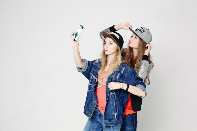 Twee swag zusters nemen zelfportret op telefoon.
