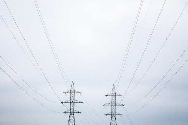 Twee symmetrische metalen elektrische torens met draden