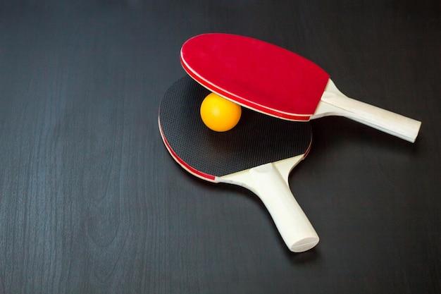 Twee tafeltennis of ping pong rackets en bal op een zwarte achtergrond