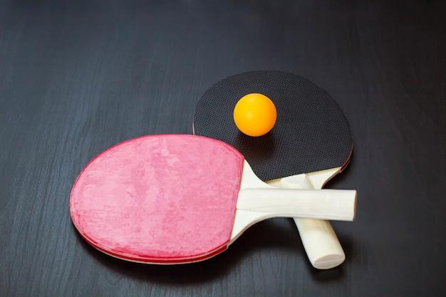 Twee tafeltennis of pingpongrackets en bal op een zwarte achtergrond