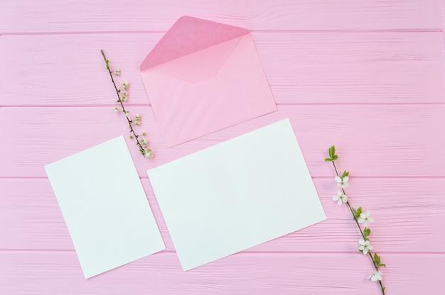 Twee takken van witte kersen bloemen op roze houten achtergrond met vel papier