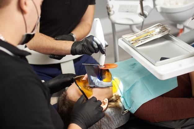 Twee tandartsen bevestigen de tanden van een patiënt met een kofferdam op het gezicht