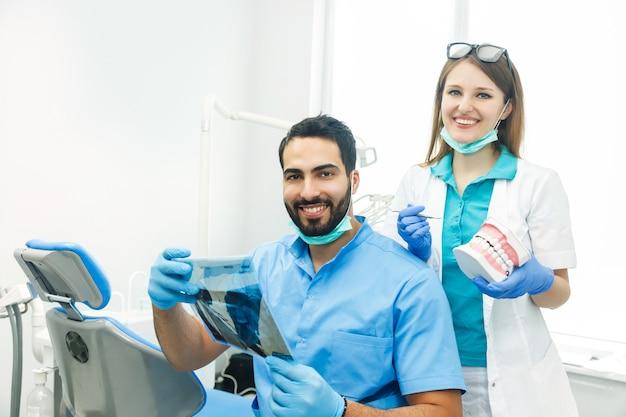 Twee tandartsen die een röntgenfoto in een kliniek bespreken