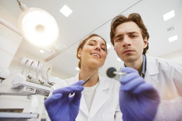 Twee tandartsen die patiënt onderzoeken