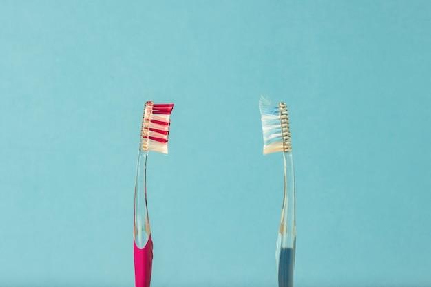 Twee tandenborstels, nieuw en gebruikt, op een blauwe achtergrond. het concept van het wisselen van tandenborstels, mondhygiëne, tandheelkunde, vriendelijke familie.