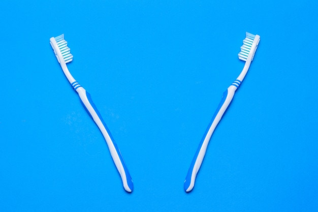 Twee tandenborstels op een blauwe achtergrond. het uitzicht vanaf de top. plat liggen.