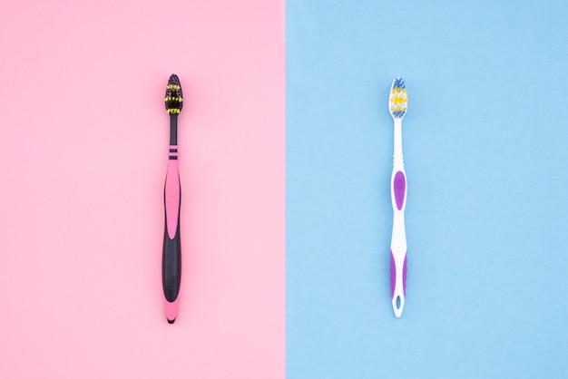 Twee tandenborstels op roze en blauw. plat liggen
