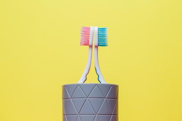 Twee tandenborstels staan met een grijs glas op een gele achtergrond.
