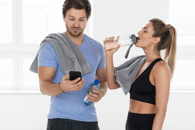 Twee teamgenoten in de sportschool na een zware training. de man onderzoekt de smartphone en de vrouw drinkt het water.