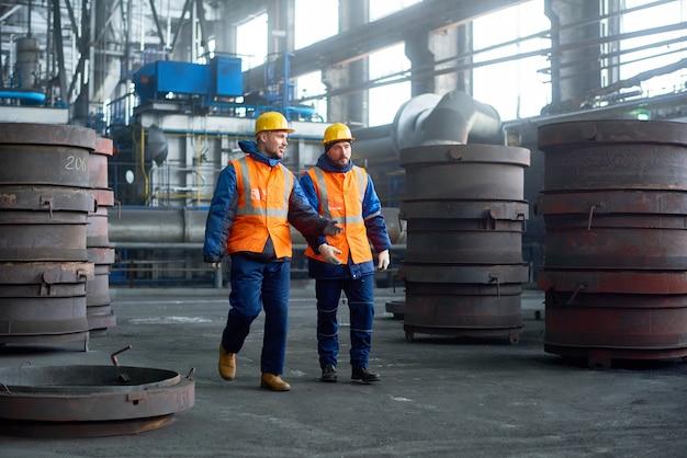 Twee technici lopen langs de productieafdeling