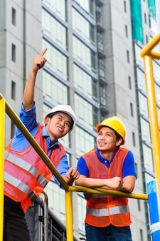 Twee technici of ingenieurs die op een industriële site werken