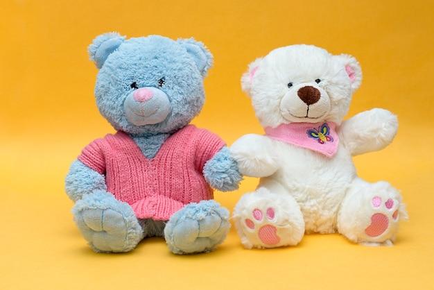 Twee teddyberen houden elkaars hand vast
