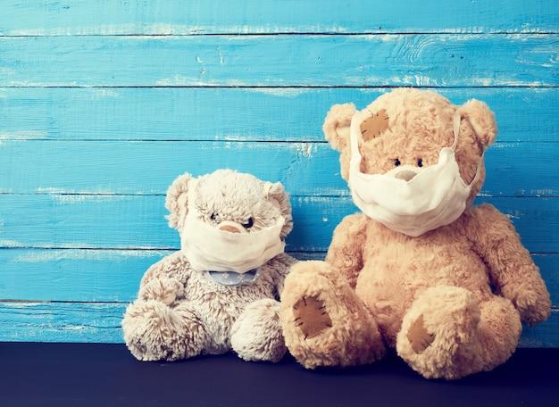 Twee teddyberen zitten in witte medische maskers