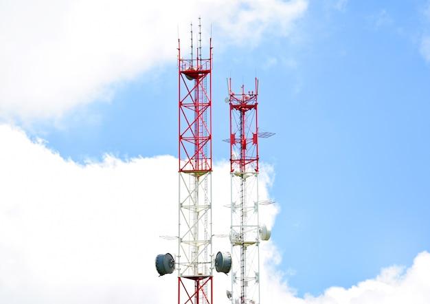Twee telecommunicatietorens met radiomodules en antennes tegen een achtergrond van blauwe lucht en wolken. slimme antennes zenden 4g- en 5g-cellulaire signalen naar consumenten.