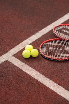 Twee tennisrackets die door witte lijn dichtbij drie gele ballen liggen