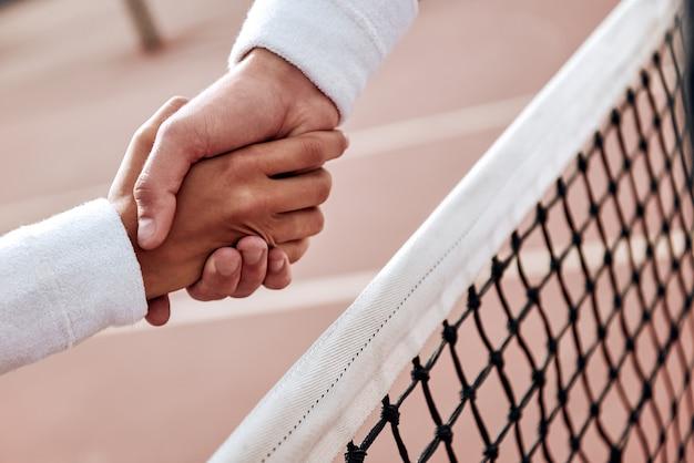 Twee tennissers schudden elkaar de hand