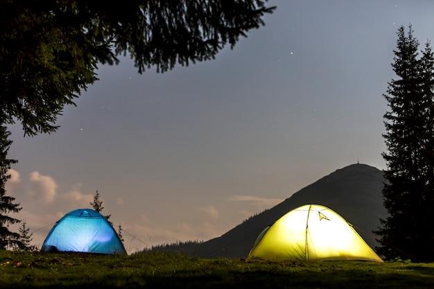 Twee tenten op bosopheldering op verre bergachtergrond.