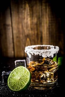 Twee tequila shotglazen op donkere tafel, met ijsblokjes, zout en limoenen