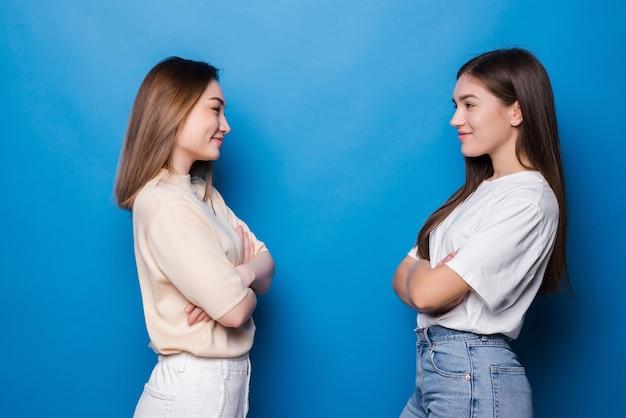 Twee tevreden meisjes kijken elkaar aan over een blauwe muur