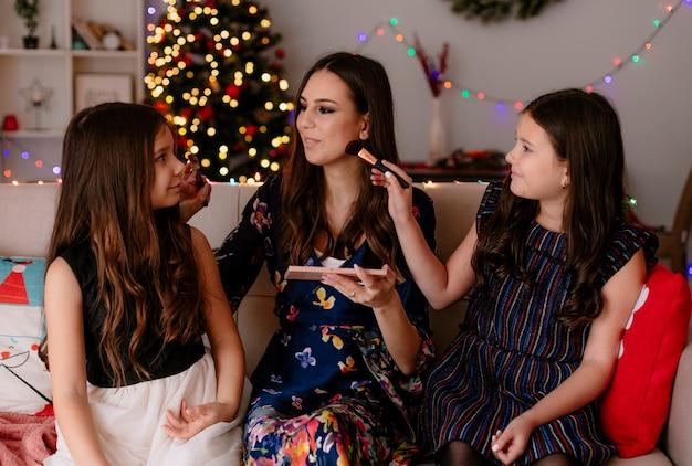 Twee tevreden zussen en jonge tevreden moeder thuis in de kersttijd zittend op de bank in de woonkamer make-up op elkaar te zetten terwijl ze naar elkaar kijken
