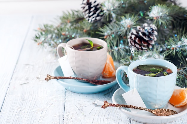 Twee theekopjes met theezakje en kerstboom
