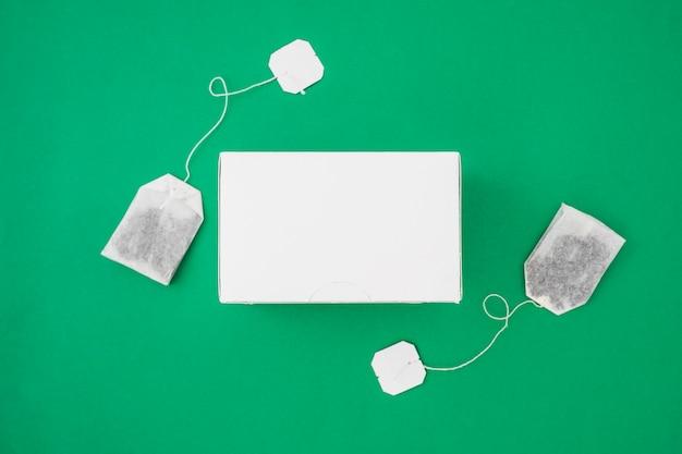 Twee theezakjes aan de kant van witte doos over de groene achtergrond
